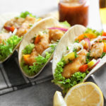 Stand with delicious fish tacos on table