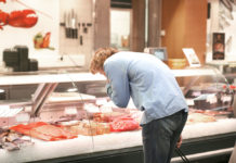 Man shopping for fresh fish seafood in supermarket