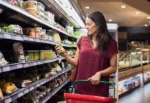 Woman checking food label in supermarket