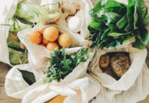 Fresh vegetables in eco cotton bags on table in the kitchen