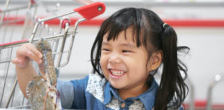 Young girl holding fresh crab at grocery store