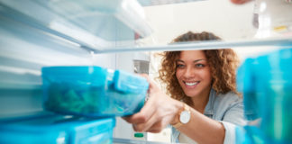 Woman taking prepped meals out of fridge