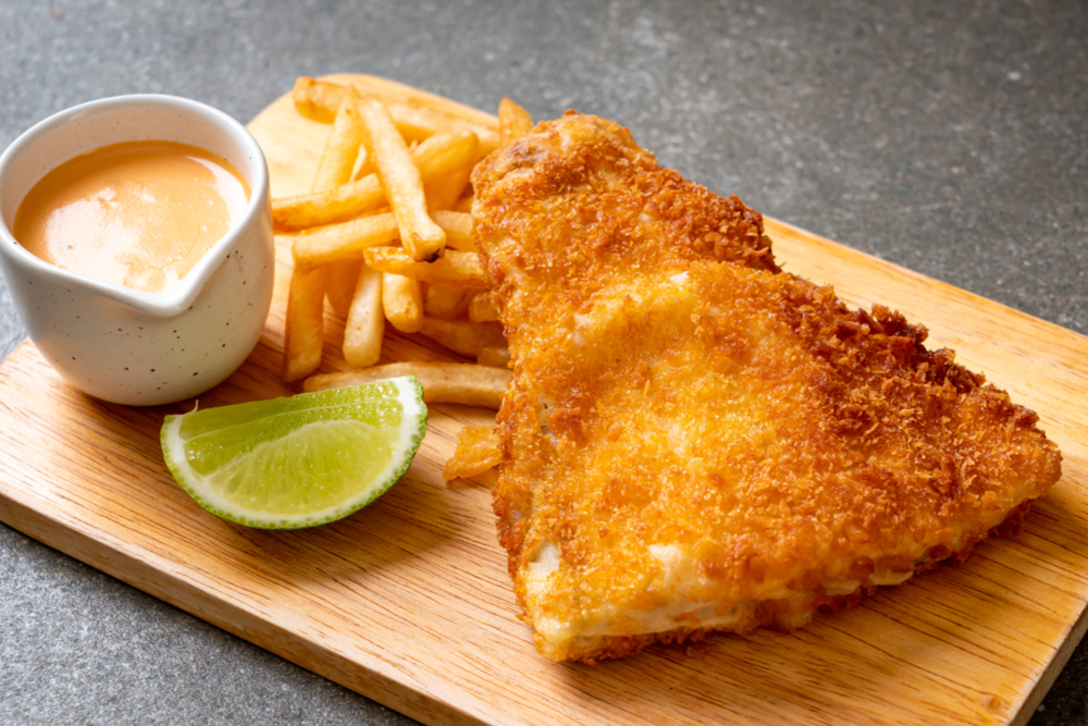 Air fryer fish and chips dish with sauce and lime