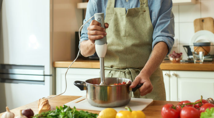 Man using a hand blender to prepare a meal