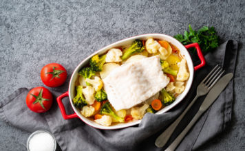 Prepping fish with vegetables to go in the oven
