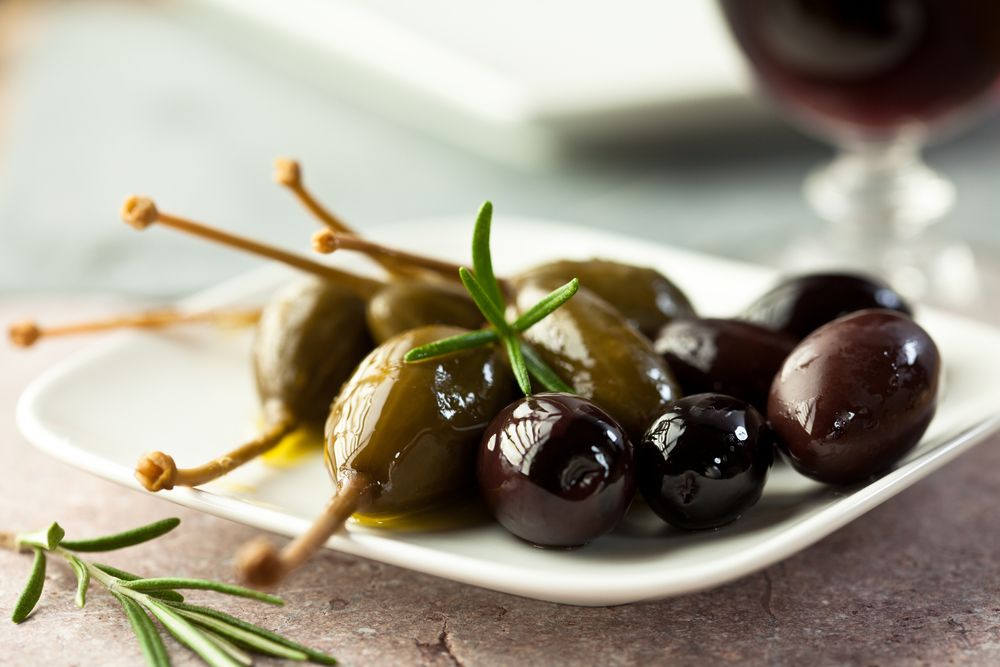 Caper berries and olives on a plate
